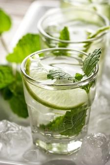 Saludable sabrosa refrescante fresca desintoxicación de agua en vasos con cal, menta y hielo sobre fondo de madera. De cerca. Concepto De Vida Saludable.