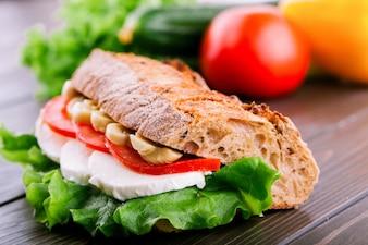 Sándwich de pan integral crujiente con champiñones, tomates, huevos y ensalada