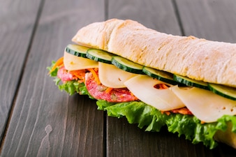 Sándwich de pan integral crujiente con pepinos, queso, salami y ensalada verde