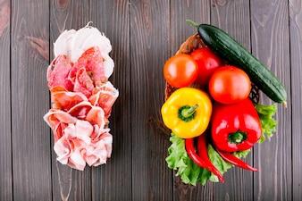 Sandwich de rebanadas de carne ahumada y aceitunas se encuentra antes de canasta con verduras frescas