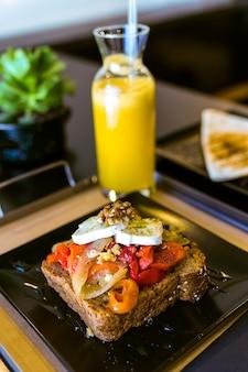 Sandwich saludable con frutas y nueces y jugo de naranja en un restaurante.