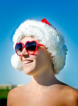 Santa chica con gafas de sol en forma de corazón
