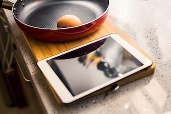Sartén con huevo y una tablet