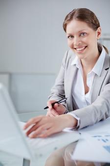 Secretaria escribiendo en el ordenador y sujetando un bolígrafo