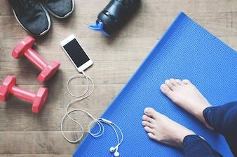 Selfie de pies mujer de yoga, smartphone, equipos deportivos y zapatos de deporte en piso de madera