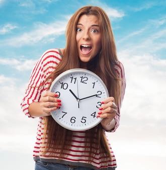 Señora atractiva con el reloj redondo en las manos.