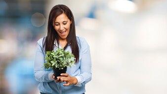 Señora joven admirando su planta