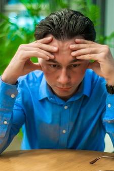 Sentirse cansado. Frustrado joven manteniendo los ojos cerrados mientras estaba sentado en su lugar de trabajo en la oficina