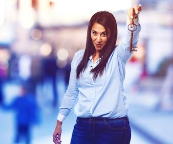 Señora joven sonriente mostrando una llave antigua