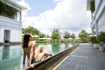 Serena joven tomando el sol en la piscina del hotel