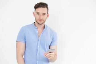 Serio apuesto joven utilizando teléfono inteligente
