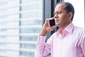 Serio, indio, hombre, Hablar, teléfono, ventana