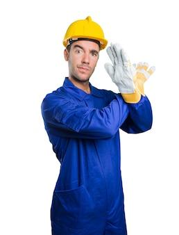 Serio trabajador haciendo un gesto de prohibición sobre fondo blanco