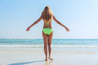 Sexy bikini cuerpo mujer asiática juguetón en el paraíso playa tropical divertirse jugando salpicando el agua en la libertad con los brazos abiertos. Muchacha hermosa del cuerpo del ajuste en vacaciones del recorrido. Banner de cultivo para el espacio de la copia.