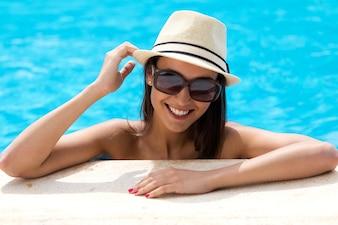 Sexy chica de pie en la piscina.