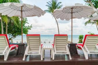 Sillas de playa hermosa con el paraguas en torno a caca de natación al aire libre