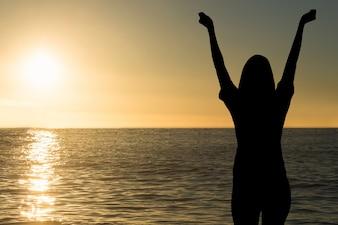 Silueta de mujer en la playa al atardecer