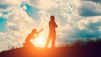 Silueta del hombre enfadado con su esposa arrodillada