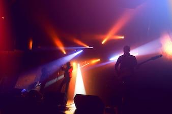 Siluetas de banda de rock en el escenario en el concierto.