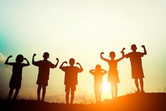 Siluetas de niños mostrando músculos al atardecer