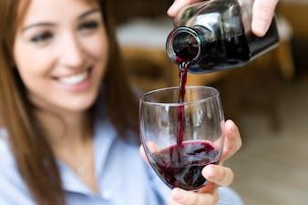 Sirva el vino tinto en el vaso de una chica bonita.