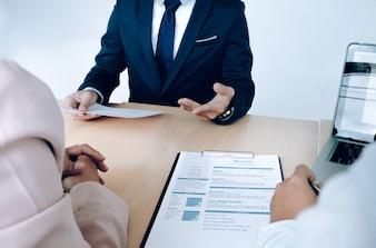 Situación empresarial, concepto de entrevista de trabajo. Buscador de empleo presenta curriculum vitae a los gerentes.