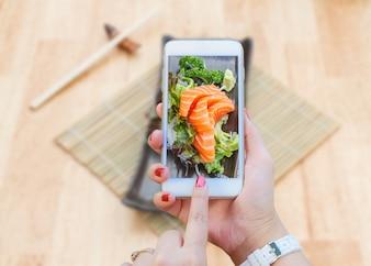Smartphone tomando salmón Sashimi