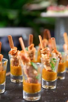 Snacks deliciosa carne con la salsa en vasos de medida