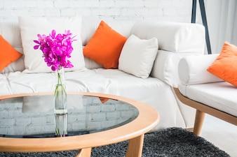 Sofá con cojines y una mesa de cristal