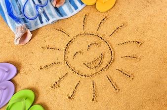 Sol feliz dibujado en la arena