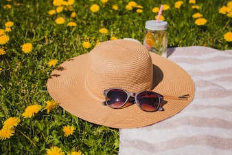 Sombrero y gafas de sol en el césped con flores amarillas