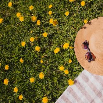Sombrero y gafas de sol en el césped con flores