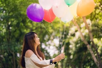 Sonriendo a las mujeres asiáticas hermosas jovenes con el pelo marrón largo en el parque. Con los globos de aire de color arco iris en sus manos. Una energía positiva y natural de la naturaleza.