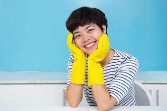 Sonriente ama de casa en guantes de protección en la cocina