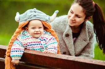 Sonriente bebé y la madre sentada en el banco