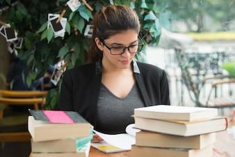 Sonriente estudiante femenina lectura copybook en la mesa