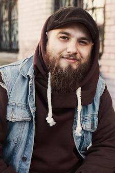 Sonriente hombre con barba con un chaleco vaquero