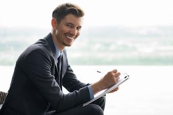 Sonriente hombre de negocios que hace notas de edad media