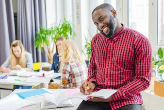 Sonriente hombre negro posando con bloc de notas