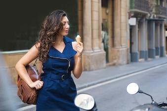 Sonriente joven comiendo helado en moto