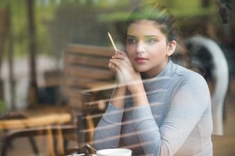 Sonriente joven estudiante con lápiz sentado en el café