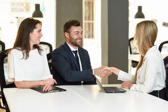 Sonriente joven pareja agitando las manos con un agente de seguros