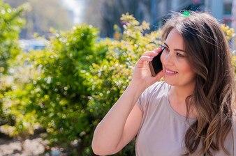 Sonriente joven y bella mujer hablando por teléfono inteligente en la ciudad. Tecnología, comunicación, estilo de vida y concepto de la gente - sonriente joven llamando a smartphone en la calle de la ciudad