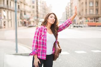 Sonriente mujer hermosa agitando a taxi