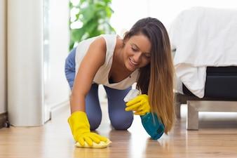 Sonriente mujer joven limpiando el piso