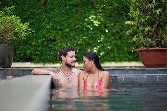 Sonriente, multi-étnico, pareja, relajante, piscina, borde
