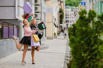 Sonriente rubia niñas con bolsas de compra de pie