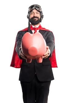 Super héroe hombre de negocios la celebración de un piggybank