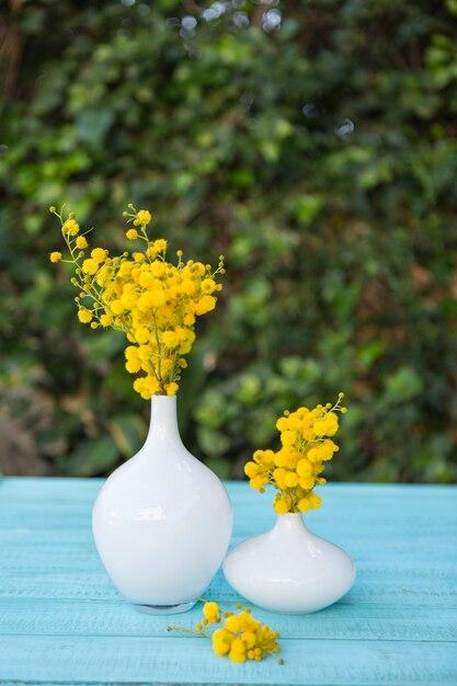 superficie azul con jarrones y flores amarillas