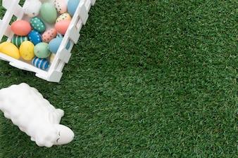 Superficie de hierba con huevos de colores y oveja para el día de pascua